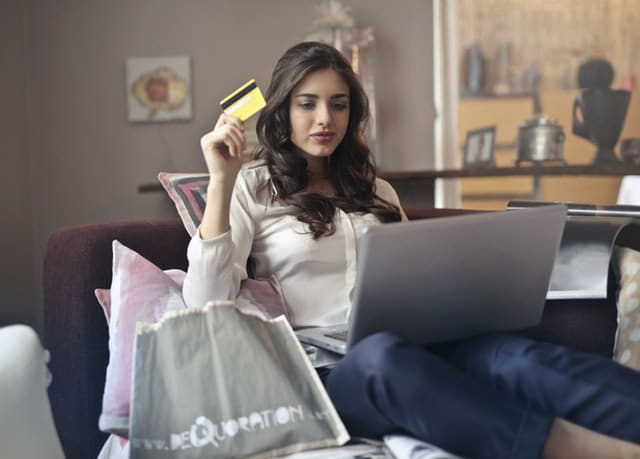 Woman shopping online with a credit card. Credit counseling can help you control impulse spending.