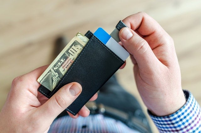 Man checking the contents of his wallet. Credit counseling can help you budget your spending money so you can pay off debt faster.