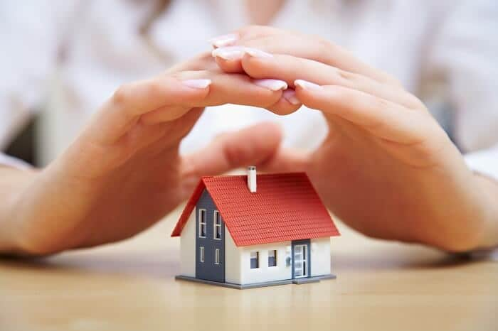 hands above a miniature house to represent home insurance