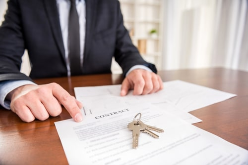 Escrow officer showing contract with key from new house