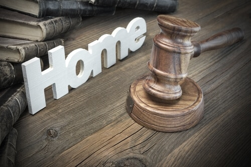 gavel and home sign on wooden surface