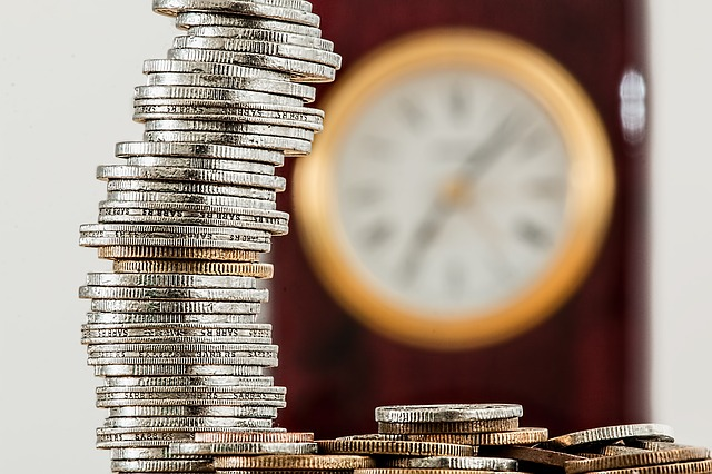 Understanding amortization could save you money this image shows a stack of coins in the foreground and a clock blurred in the background