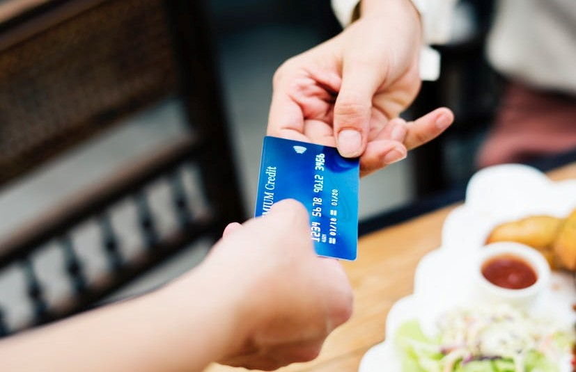 a person handing a credit card to another person