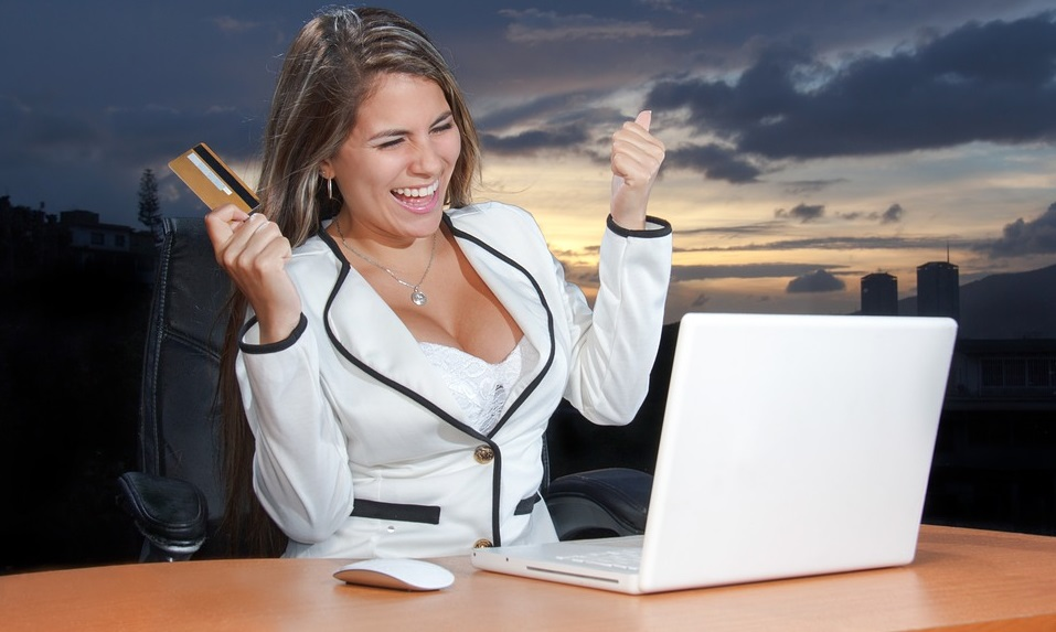a happy woman holding a credit card sitting in front of her laptop