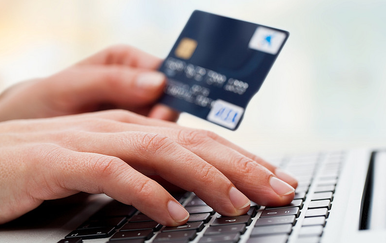 a person holding a credit card and touching the keyboard
