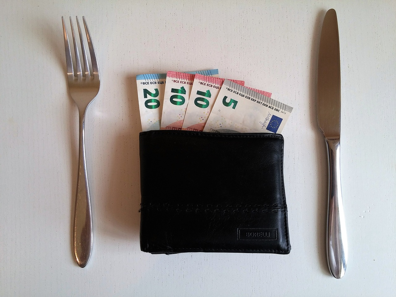 money in a wallet and fork and knife placed on right ang left sides