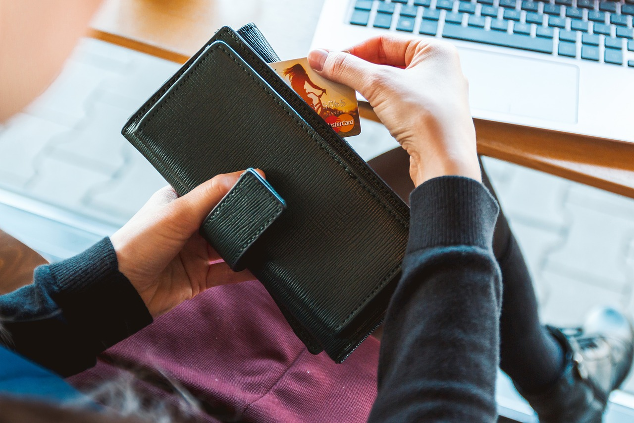 person checking a credit card on a wallet