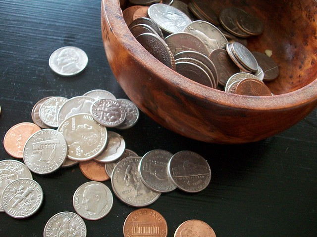 spread coins in a bowl and in the table